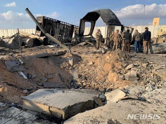 ▲ 미 군인들과 기자들이 2020년 1월 13일(현지시간) 이라크 아인알아사드 공군기지에 남은 미사일 흔적 옆에 서 있다. 이 기지는 지난 8일 이란의 '가셈 솔레이마니 폭살' 보복공습을 받았다. [사진 : 뉴시스]